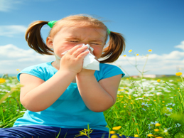 girl sneezing with spring seasonal allergy